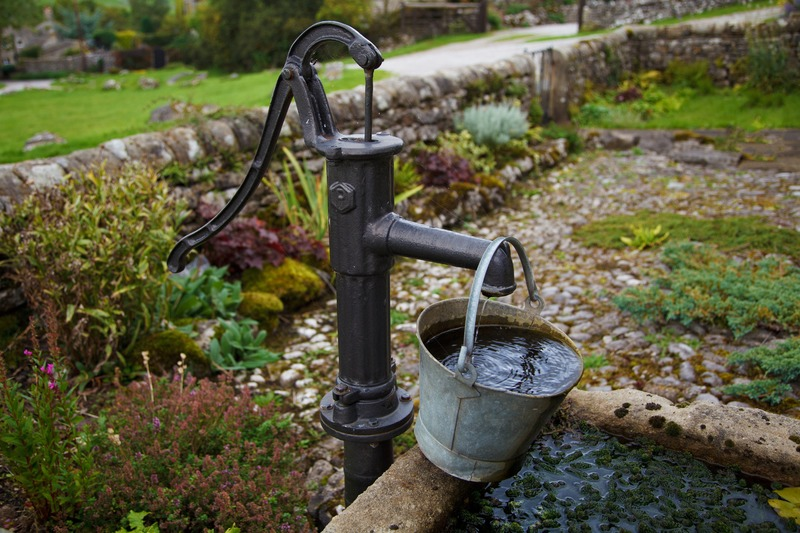 Old fashioned water hand water pump with pail hanging from it